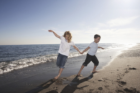 Boy and girl running on beach LANG_EVOIMAGES