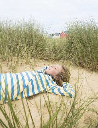 rejoices: Boy lying in dunes