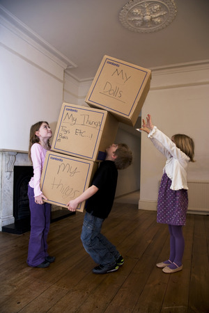 ceased: Three children moving a stack of boxes LANG_EVOIMAGES