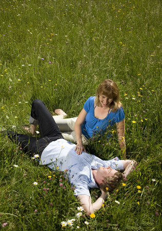 leans on hand: man, woman lying in grass with flowers LANG_EVOIMAGES