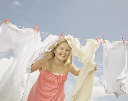 ahorcada: Chica mirando a través de una línea de lavado LANG_EVOIMAGES