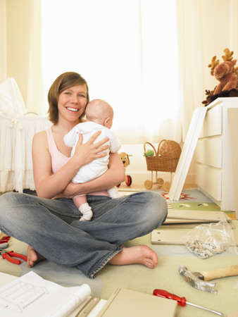 cuddled: Woman with baby building furniture LANG_EVOIMAGES