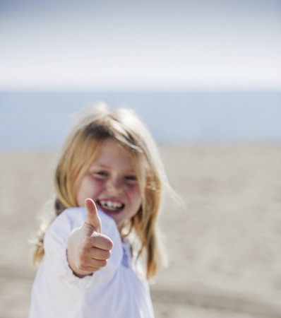 Girl at beach with thumb up to camera LANG_EVOIMAGES
