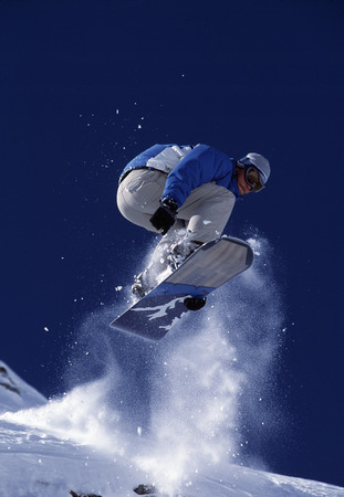agachado: Snowboarder saltando en el aire.