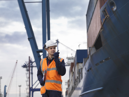 shipped: Port Worker Beside Loaded Ship LANG_EVOIMAGES