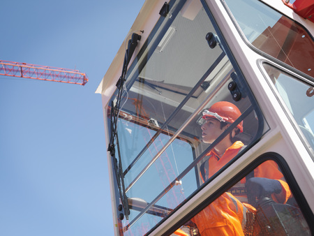 power operated: Worker Controlling Crane From Cabin