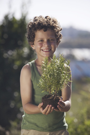 accurately: Young boy holding small plant LANG_EVOIMAGES