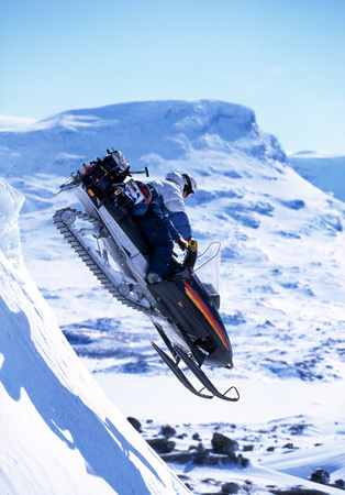perilous: Snowboarder jumping on a skidoo. LANG_EVOIMAGES