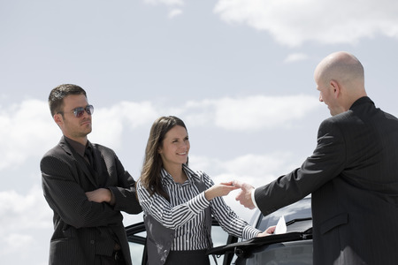agrees: man signing contract on back of car
