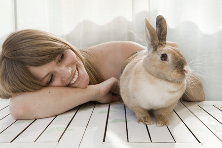 Young woman and a pet rabbit on a patio