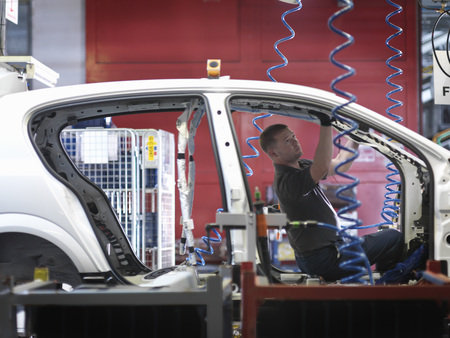 assembled: Worker Assembling Car On Production Line LANG_EVOIMAGES
