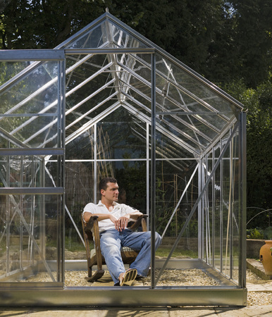 conservatories: Man relaxing in greenhouse LANG_EVOIMAGES