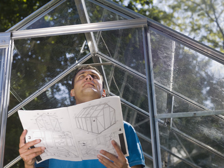 advances: Man with greenhouse plans in garden LANG_EVOIMAGES