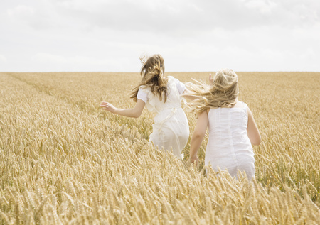 in twos: Girls running in wheat field