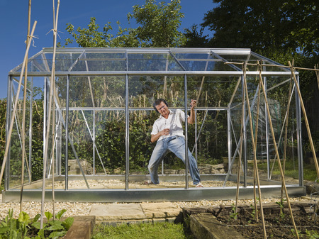 conservatories: Man playing air guitar in greenhouse