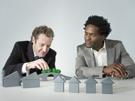 Two business men play with a train LANG_EVOIMAGES