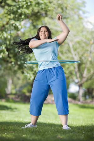 obesidad infantil: young plump girl doing hula hoop