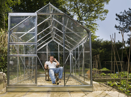 conservatories: Man relaxing in greenhouse with music