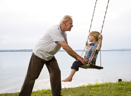 grandfather with grandson on swing LANG_EVOIMAGES
