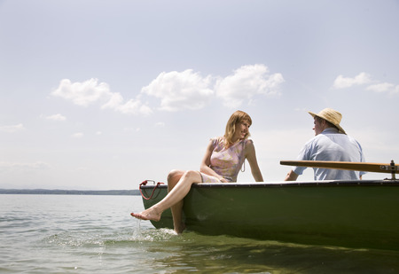 tans: man, woman in rowing boat on lake