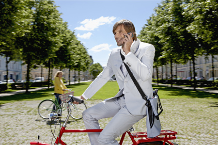 Man bicycling, talking on the phone