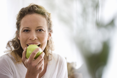 morsels: middle-aged woman eating a apple LANG_EVOIMAGES