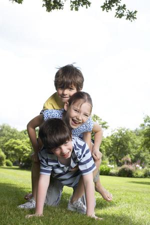 agachado: Niños jugando en el jardín LANG_EVOIMAGES