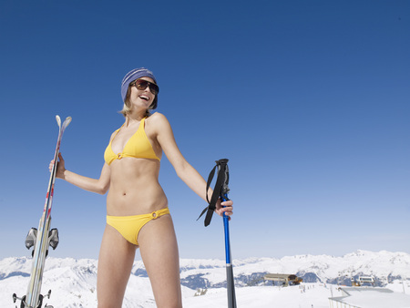 woman in bikini on mountain with skis LANG_EVOIMAGES