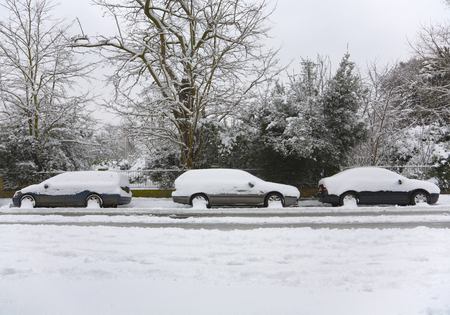 conforms: Three snow covered cars parked