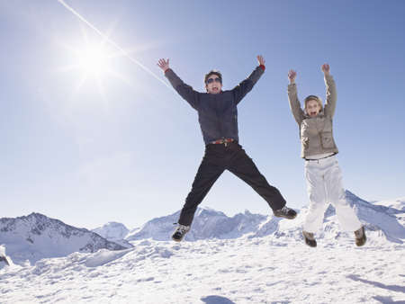 low spirited: man and woman jumping up on mountain