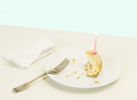 savour: half eaten birthday cake with candle LANG_EVOIMAGES