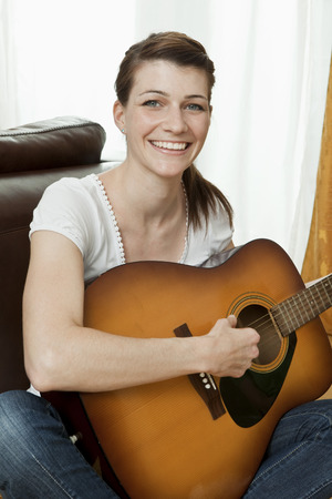 musically: Young woman playing the guitar