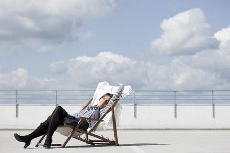 woman relaxing in deck chair LANG_EVOIMAGES