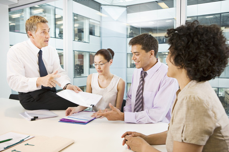 conferring: A senior male heads a business meeting
