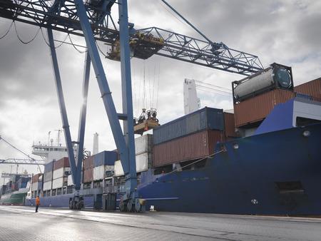 techniek: Port Worker Watching Ship Being Loaded