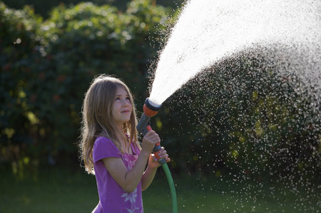 Young girl spraying water with a hose