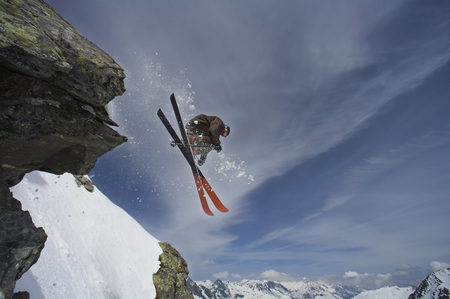Skier jumping off a rock.