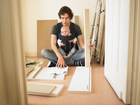 Man with baby building furniture LANG_EVOIMAGES