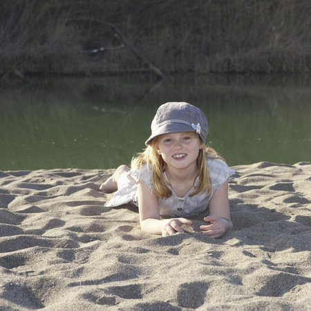 Young girl laying on sand by river