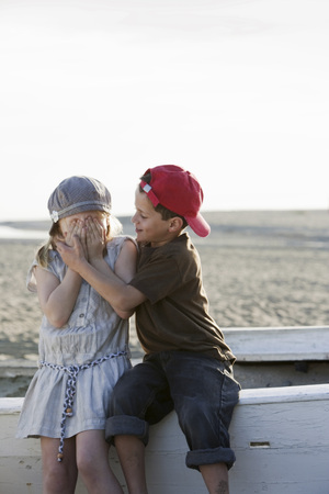 brotherly love: Boy hugging girl on small boat at beach