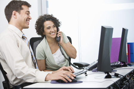 motivations: A business couple laughing at work LANG_EVOIMAGES