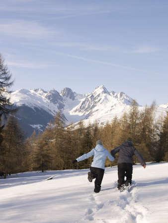 beau: couple running in snow towards mountain