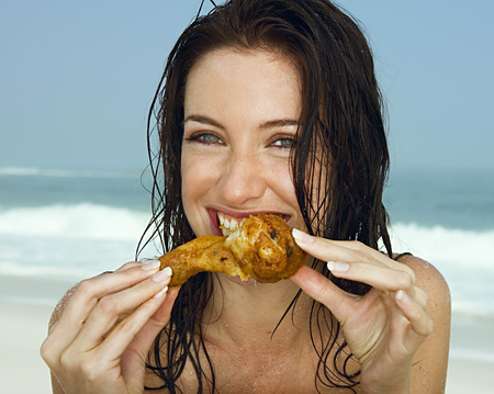 savour: Young women eating a chicken leg LANG_EVOIMAGES