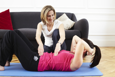 floor covering: Woman instructing a client. Pilates. LANG_EVOIMAGES