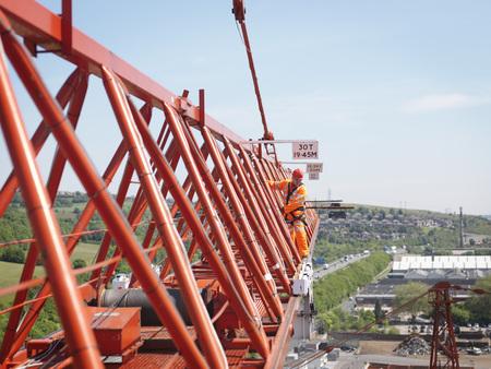 Crane Worker On Arm Of Crane
