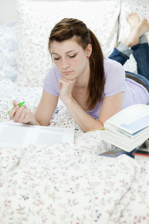 higher intelligence: Female student lying in bed, learning