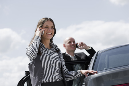 man and woman near car on the phone