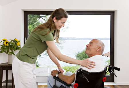 social work aged care: woman touching man in wheelchair LANG_EVOIMAGES