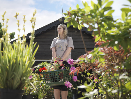 Female Buying Plants At Garden Center