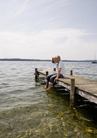 shadowed: senior man sitting on pier at lake